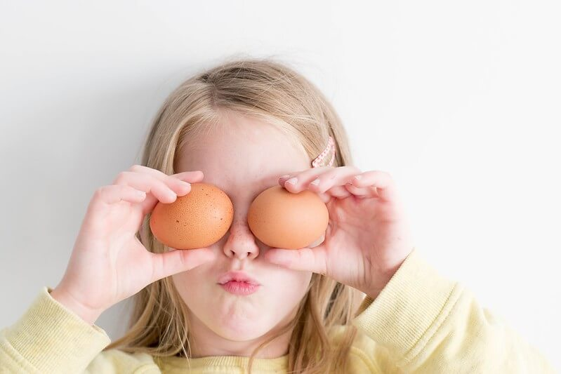 Child holding eggs that she will make into hollow eggs for the experiment