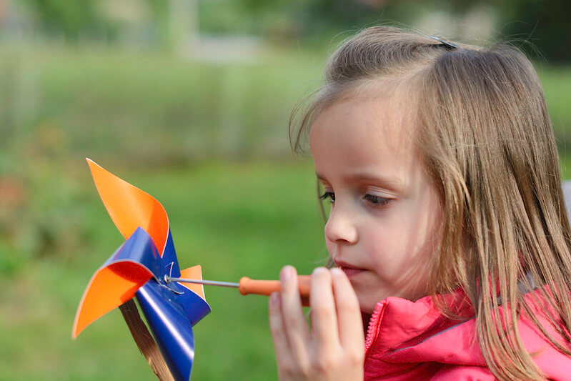Young girl making her own mini windmill.