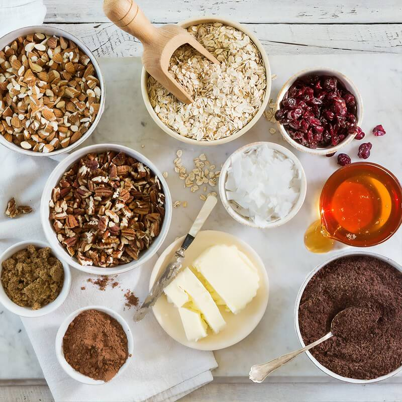 All the ingredients for vegan flapjacks laid out on the kitchen counter in separate bowls.
