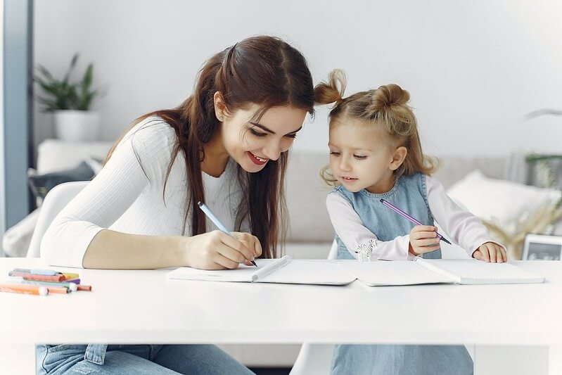 A mother showing her daughter how to write in cursive.