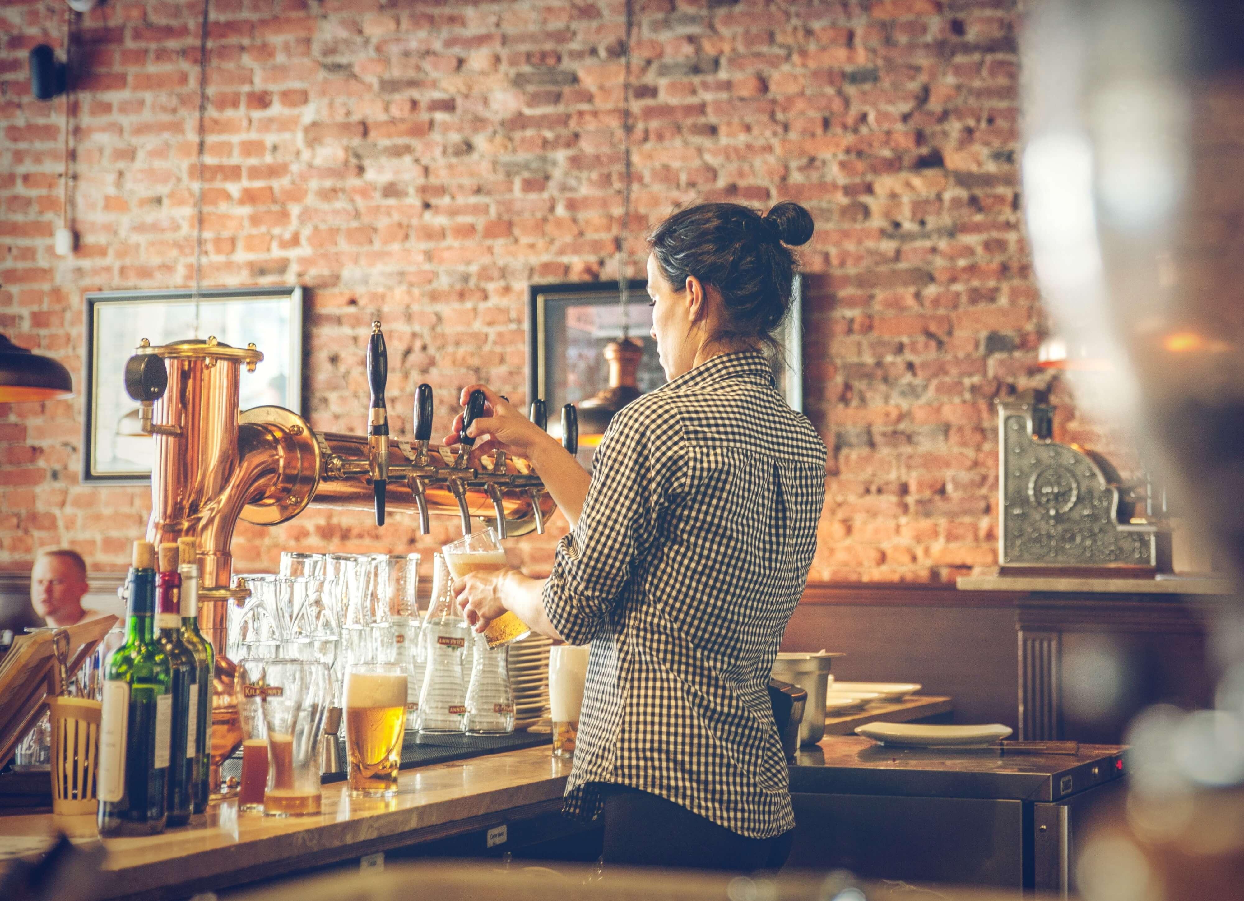 Woman Pouting Pint In A London Pub