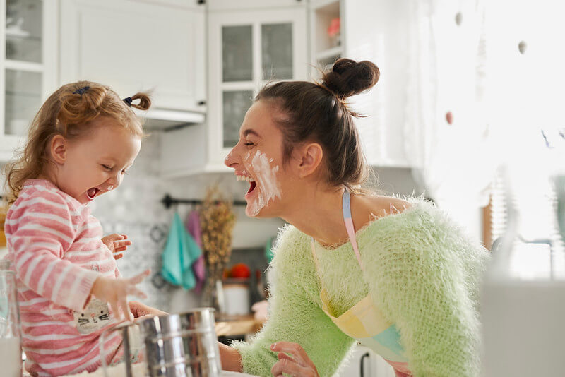 Mother and daughter getting messy in the kitchen making a cake.
