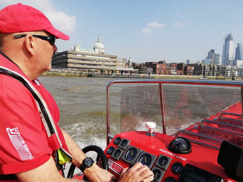 Thames Rockets skipper steering a speedboat along the Thames with St Paul's Cathedral in the background.
