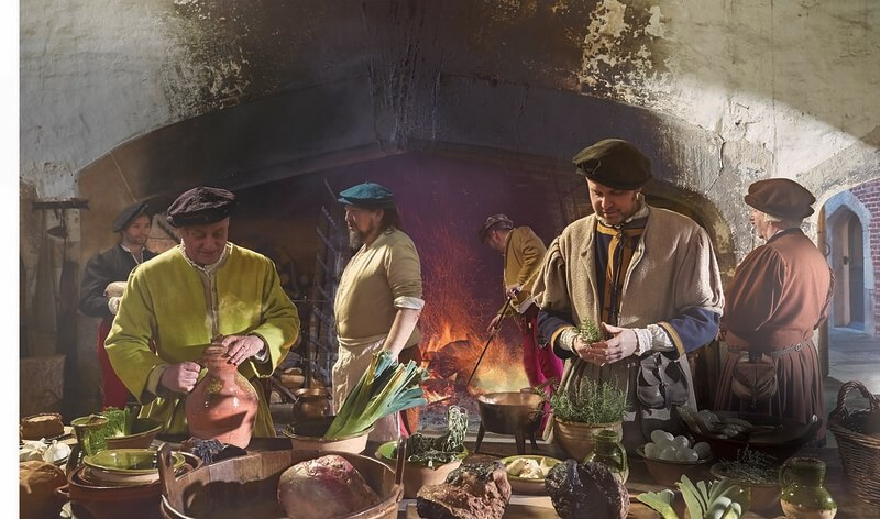Inside a tudor kitchen where food is being prepared.