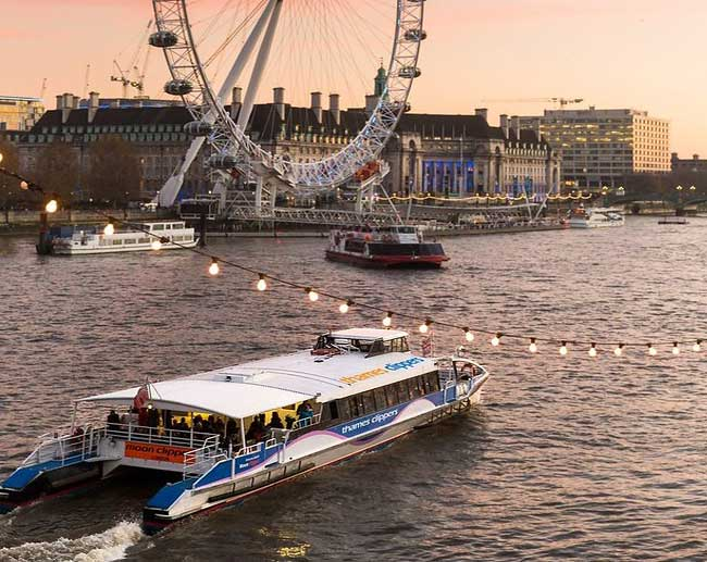Thames Clipper boat near the London Eye at sunset.