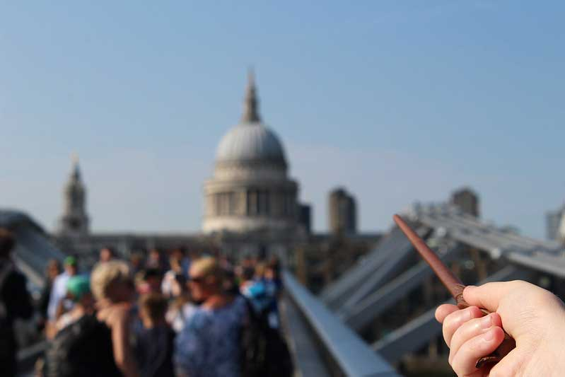 A hand pointing a wand towards St Paul's Cathedral.