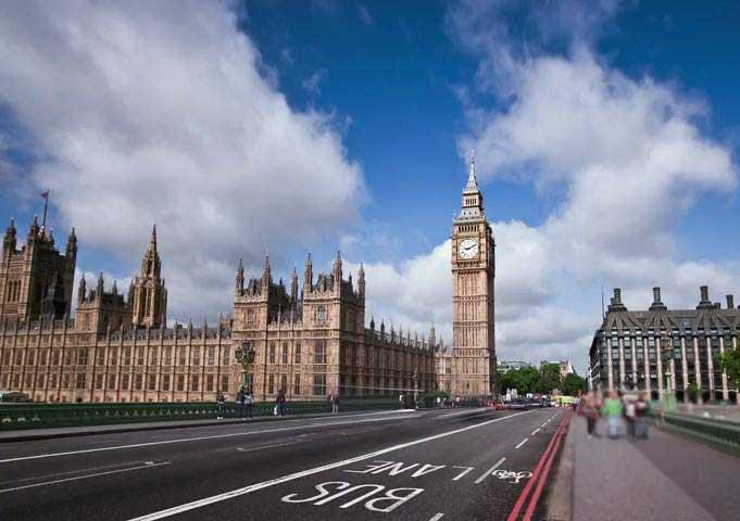 Big Ben and Westminster Bridge against a blue sky.