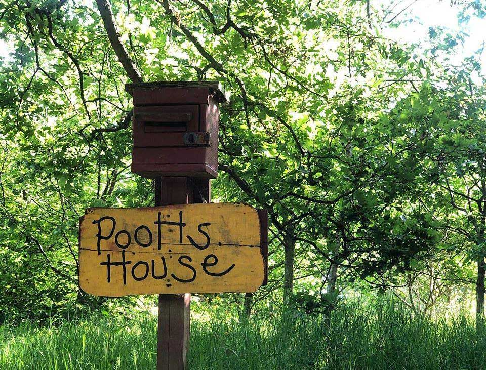 Rustic sign amongst the trees saying 'Pooh's House' in Aldenham Country Park.