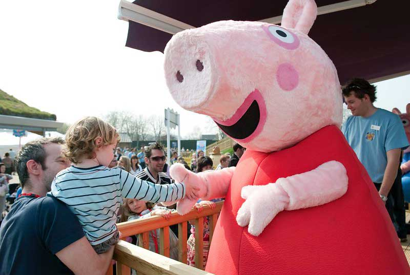 Toddler in their parent's arms meeting Peppa Pig at Paultons Park.