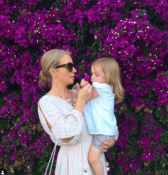 Robin Marsden and her daughter in front of a wall of flowers.