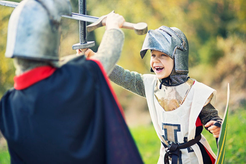 Two children dressed as knights in battle.
