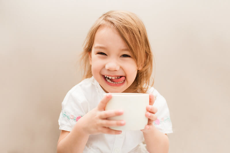 Child using a cup in tea staining experiment