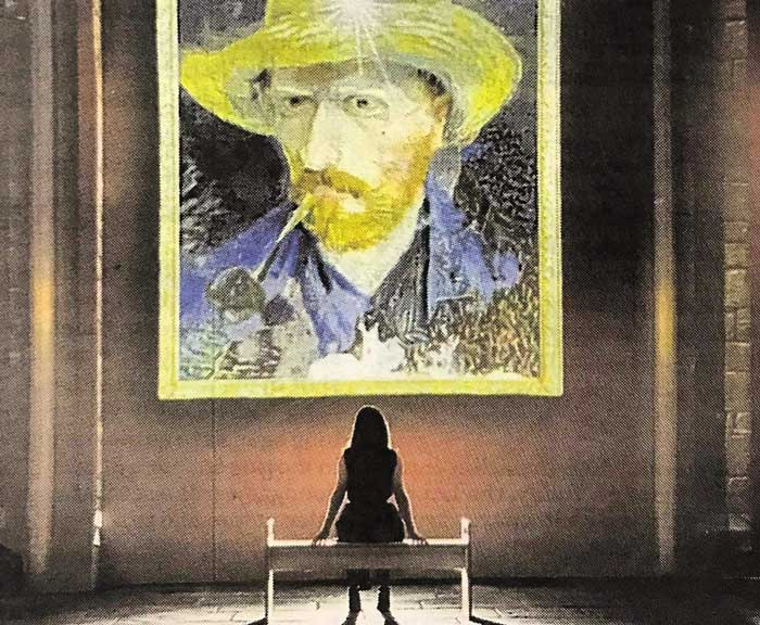 Woman sat on a bench looking up at a projection of a Van Gogh self portrait.