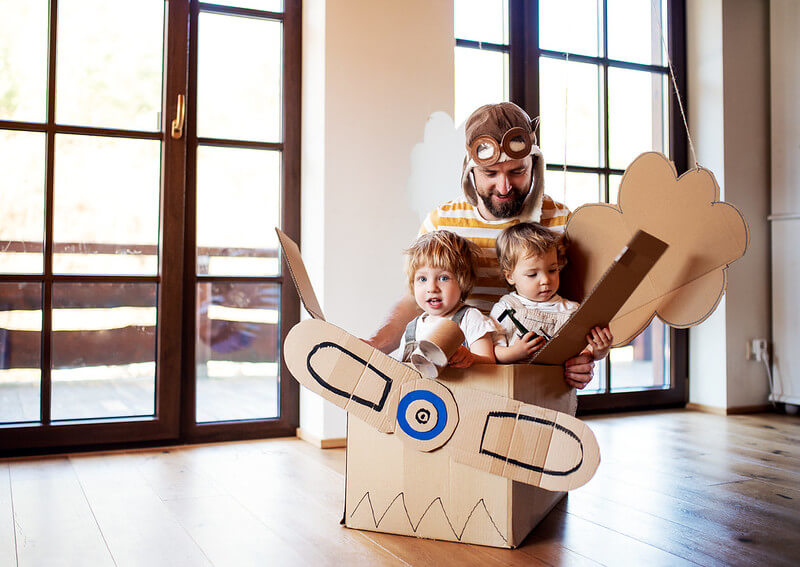 Dad telling children airplane jokes while they play in a cardboard airplane