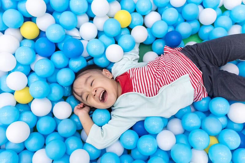 Child surrounded by glow in the dark bouncy balls you can make at home