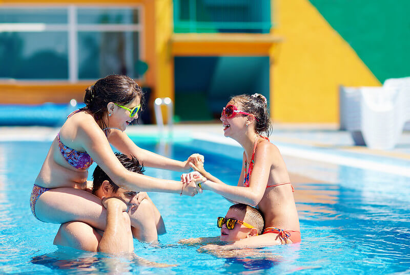 two teen girls sitting on friend's shoulders in swimming pool