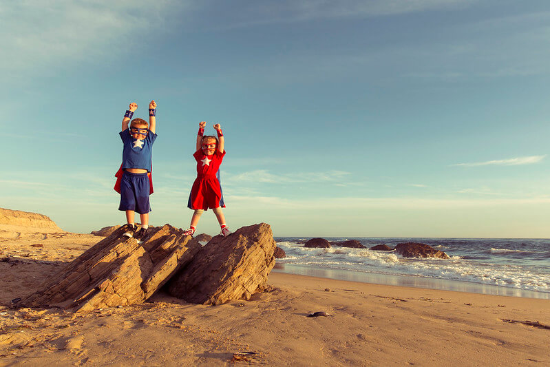 Children dressed as superheroes standing on rocks making rock puns