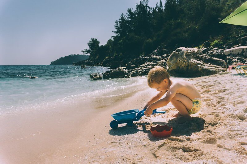 Baby playing on the beach on holiday after getting passport