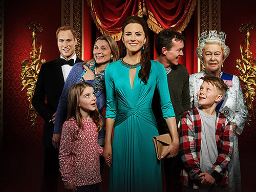 Family posing with waxwork figures of the Royal Family.