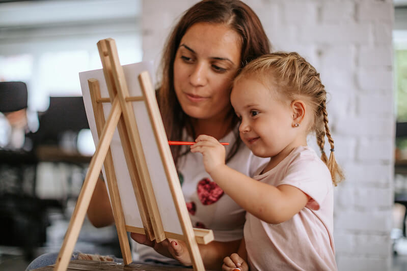 mother aiding daughter in making famous art copy for kids project