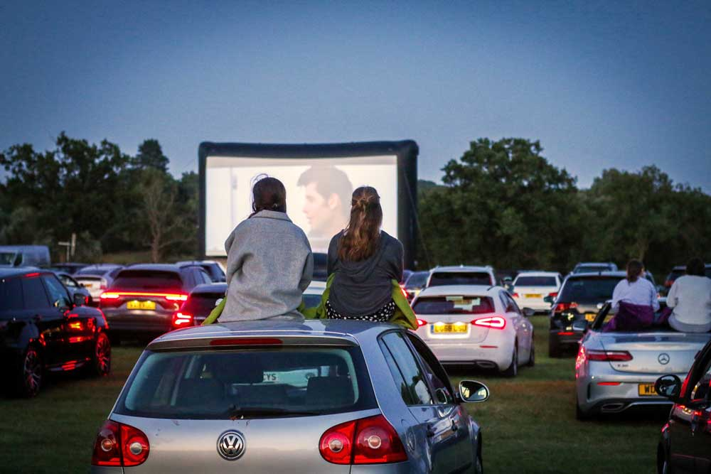 two women sat on top of car at drive-in screening