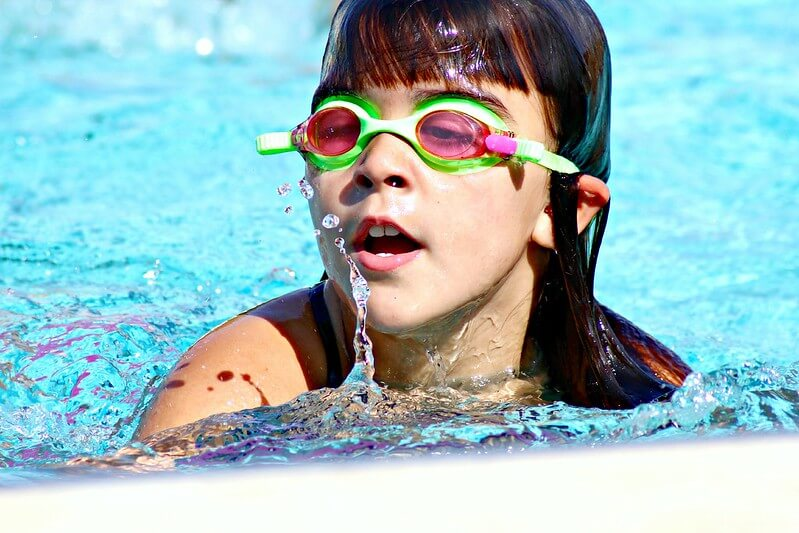 Girl in goggles swimming during the new normal in swimming pools and lidos
