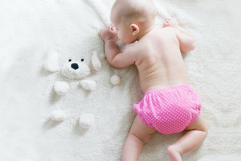 Baby girl wearing a pink nappy lying on a white fluffy blanket.