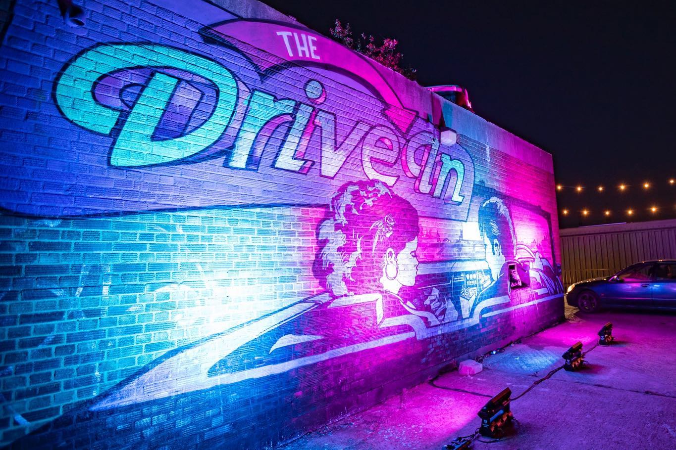 The Drive In logo projected against a wall in blue and purple.