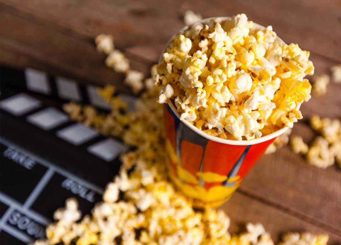 Tub of popcorn spilling out over a clapperboard.