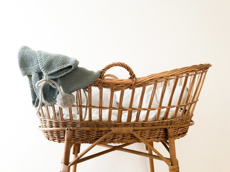 Moses basket with a knitted baby outfit draped over the side.