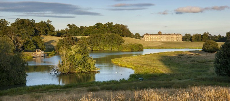 open green space with a big lake and Petworth House in the background