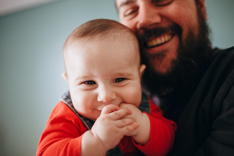 Baby Isaiah being held by his bearded father has a brilliant boys' name beginning with I.