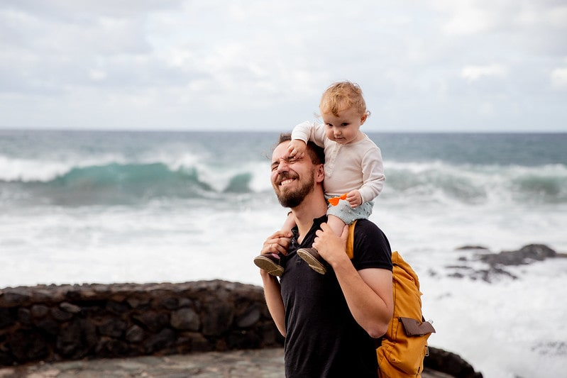 Father carrying his daughter on his shoulders by the sea, who has one of our incredible girls' names beginning with I.