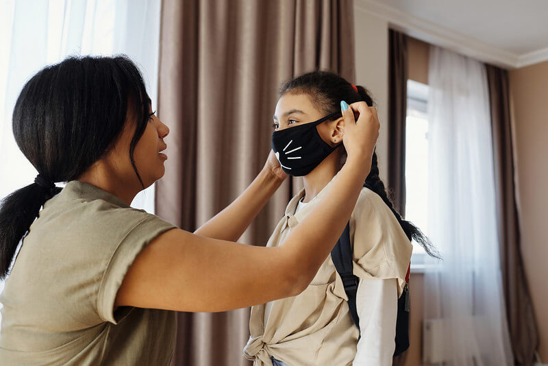 woman putting a fun COVID face mask onto her child