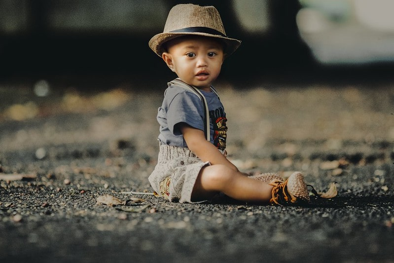 Baby boy wearing dungaree shorts and a straw hat sitting on the floor on the street.