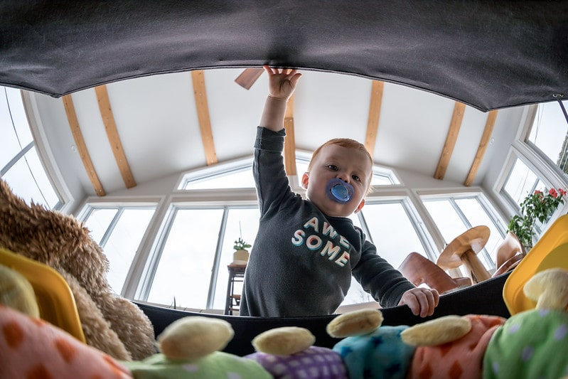 Boy with a dummy in his mouth opening the toy box and looking inside.