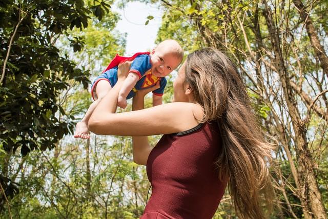 Baby dressed as Superman being spun around by mum.