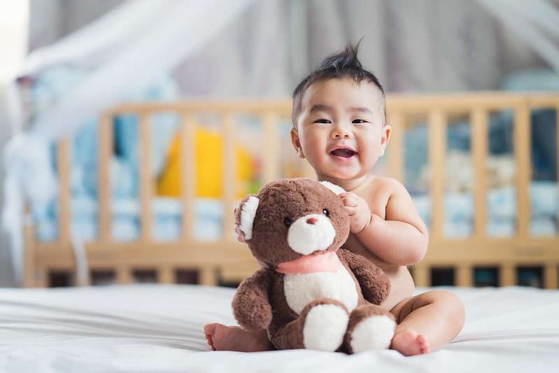 Baby boy sitting on the bed smiling with a teddy bear in arms.