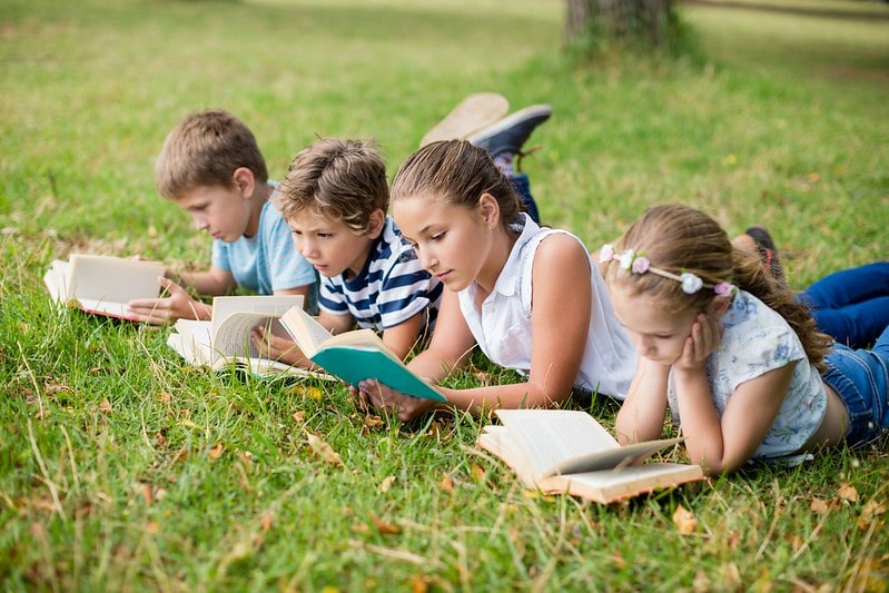 Children reading different Oxford Reading Tree levels in a field.