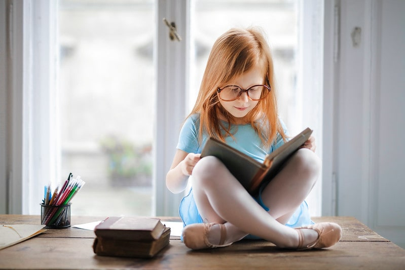 Pre-school girl reading a book from the Oxford Reading Tree