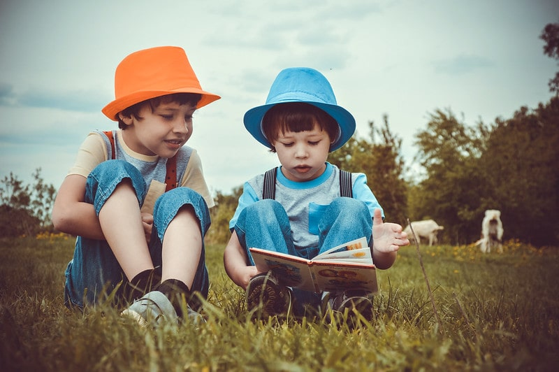 Two pre-school boys reading books as part of the Oxford Reading Tree