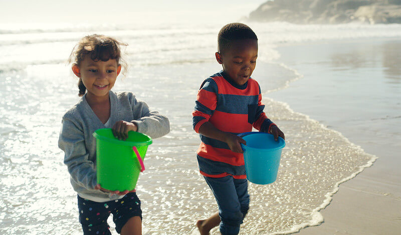 two kids with buckets on an England beach