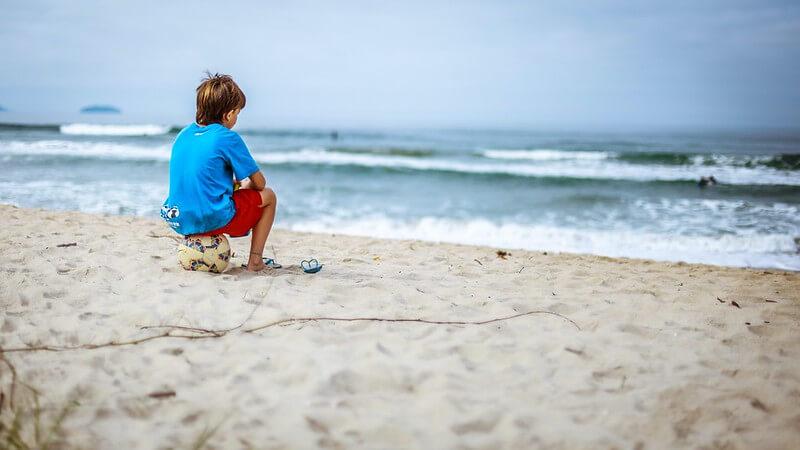 kid sitting on a football on the beach