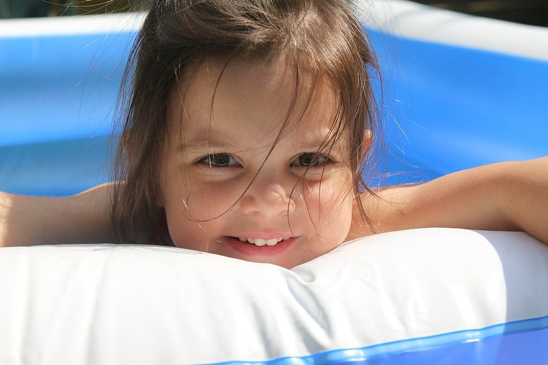 Little girl smiling while in a clean paddling pool