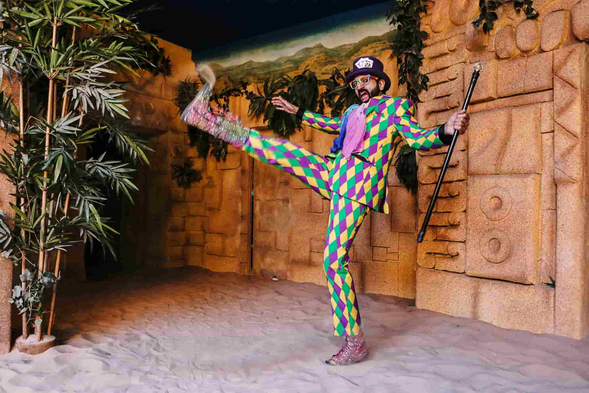 A maze master in a colourful suit posing dramatically with his leg up in the air.