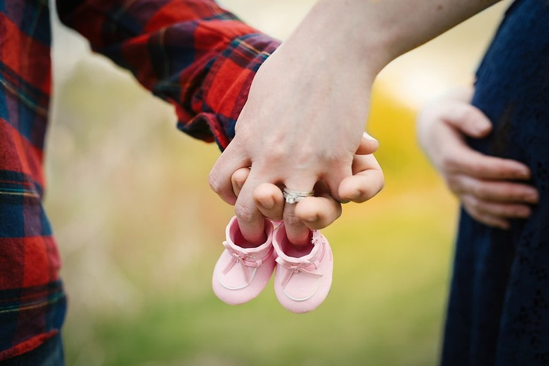 How to tell people you're pregnant could be with an announcement like this, with the parents holding pink booties.