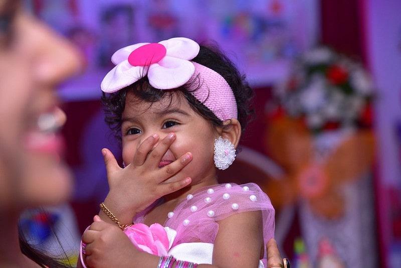 Little girl wearing big flower headband giggling at a joke.