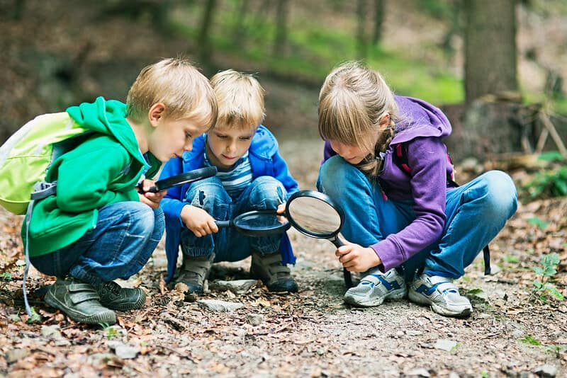 Three children with magnifying glasses looking for minibeasts in the mud
