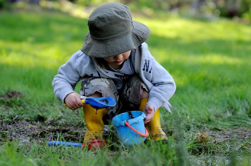 Young boy plays in the mud, enjoying the fantastic minibeasts activities