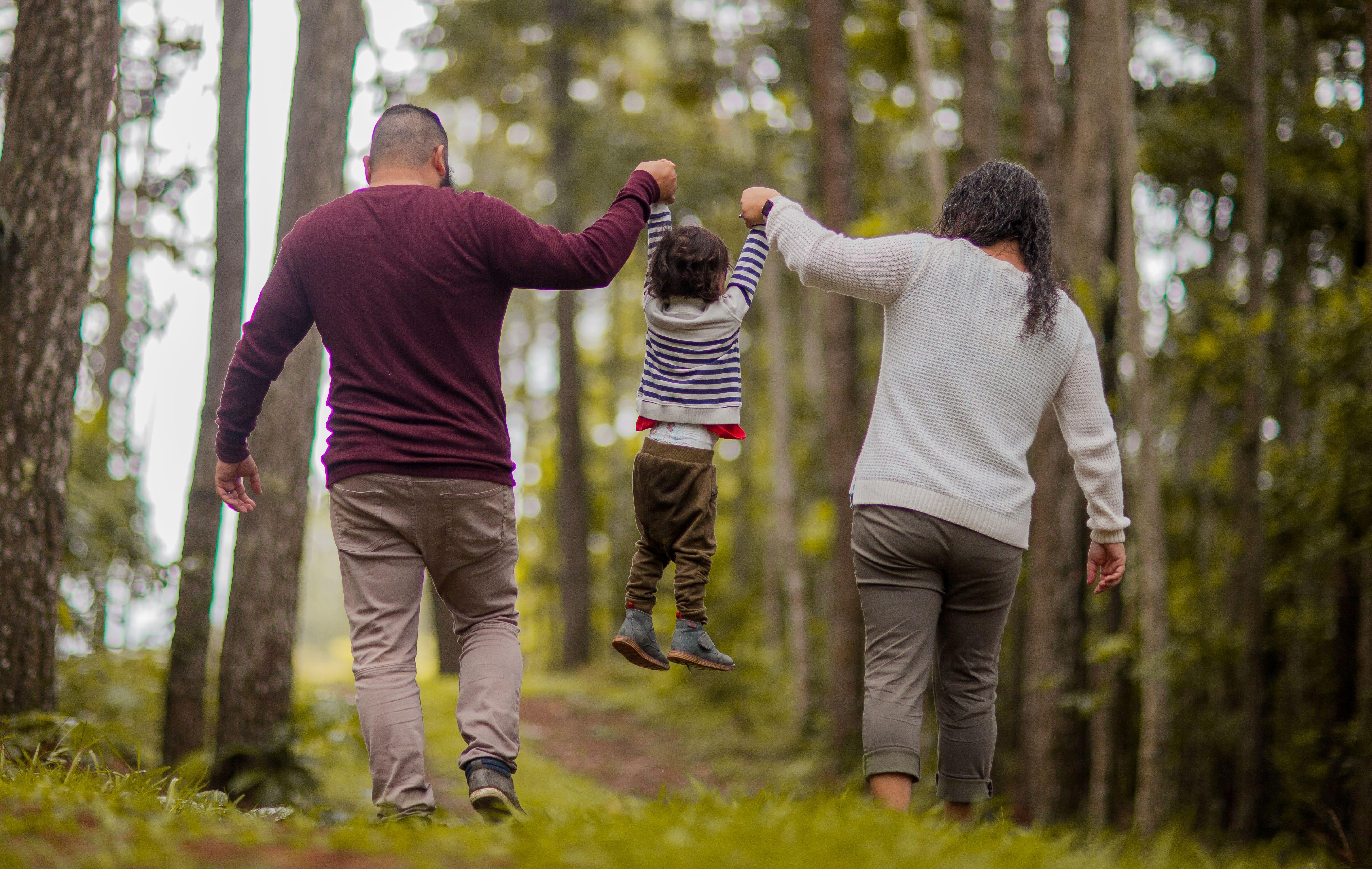 family walking in open green forest outside of London